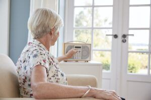 Senior woman in an armchair listening to the radio at home